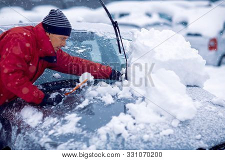 Winter Problems Of Car Drivers.man Brushing The Snow Off His Car On A Cold Winter Day