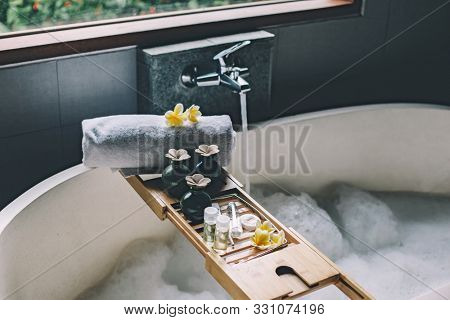 Beauty products on tray on bathtub. Bath with foam is filling with water. Relaxing in Bali luxury spa hotel.