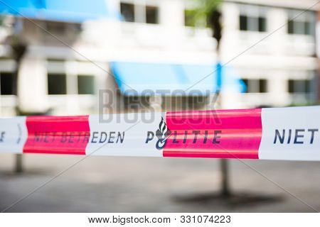 Dutch police line. Do not cross. Red plastic tape on a crime scene with text No trespassing Police