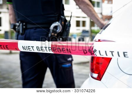 Dutch Policeman on crime scene at school. Red tape with text No trespassing Police