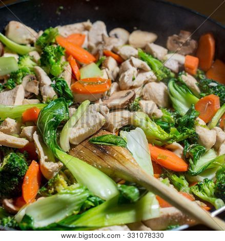 Close-up On Dinner Angle View Of Wooden Spoon Stirring Chicken And Vegetables In Cast Iron Skillet -