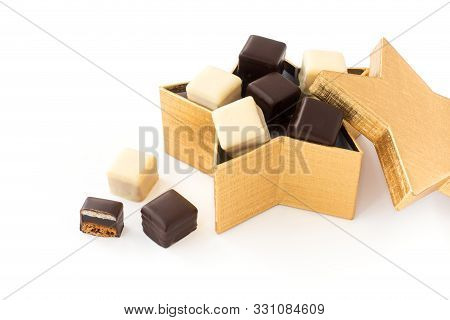 Dominosteine, A German Gingerbread, In A Golden Star Shaped Box Isolated On White. High Angle View.