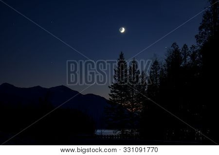 Nightscape Image Of A Quarter Moon Over Lake Mcdonald Lake In Glacier On Halloween.