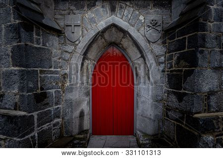 Scary Pointy Red Wooden Door In An Old And Wet Stone Wall Building With Cross, Skull And Bones At Bo