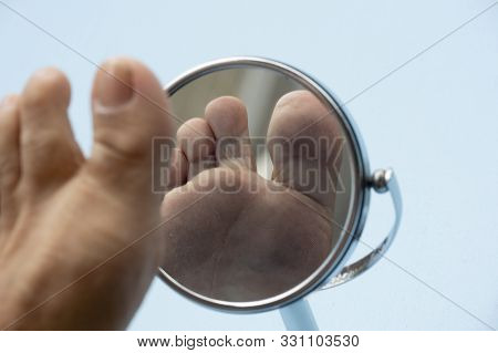 Person Looking At The Sole Of The Foot In A Mirror, To Check If There Is No Diabetic Foot, As Possib