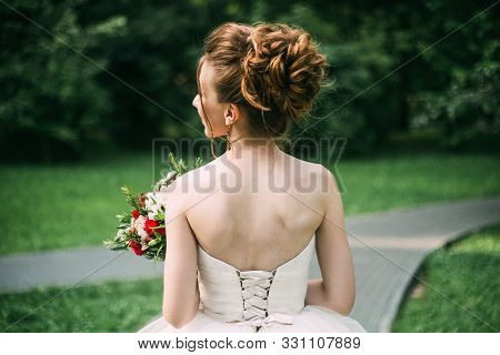 Summer Wedding Photo: A Young Slim Brown-haired Bride Bride Stands With Her Back With An Open Back I