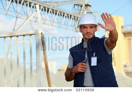 worker on a construction site waving his hand