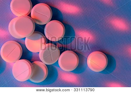 Pink Pills Over Purple Background. Pills, Drugs, Health And Medicine Concept. Abstract Colorful Back