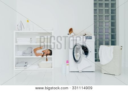 Little Tired Girl Did Work About House To Help Parents, Sleeps On Shelf Near Folded Linen, Iron And