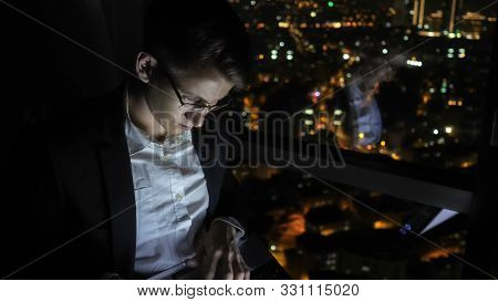 Young Man Freelancer In Glasses Is Working On His Computer Near The Window In Home At Night. Self-em