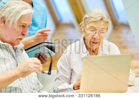 Senior couple in computer course is learning together concentrated with the laptop PC