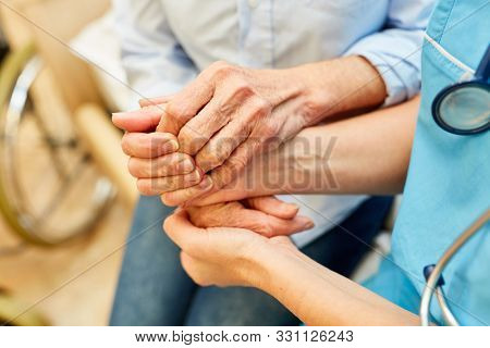 Nursing help keeps the hands of a senior citizen in a nursing home or nursing