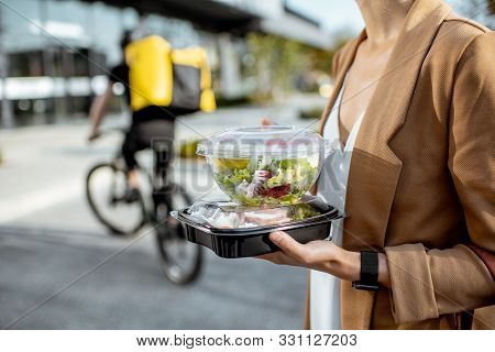 Businesswoman Holding Lunchboxes With Fresh Takaway Food Outdoors. Male Courier On A Bicycle On The