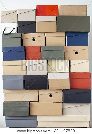 Stack Of Unevenly Folded Shoe Boxes Against A White Wall. Seasonal Sales And Discounts. Vertical Pho