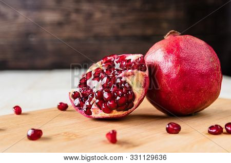 Whole Fruit And Halves Of Ripe Pomegranate Lie On A Table On A Wooden Background. Juicy Fresh Pomegr
