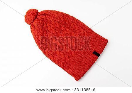 Orange Knitted Woolen Hat Beanie With Pom Pom On White Background, Winter Concept.