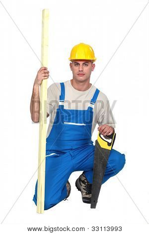 Man kneeling with saw and plank of wood