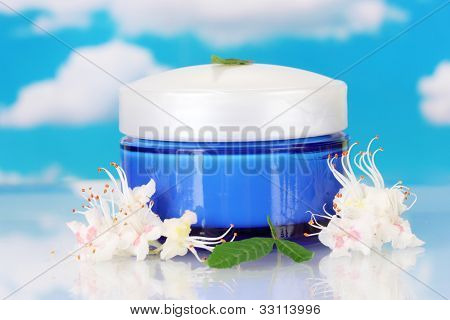 Jar of cream with chestnut flowers on sky background close-up