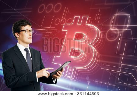 Cryptography And Innovation Concept. Young European Businessman Using Tablet On Glowing Red Bitcoin