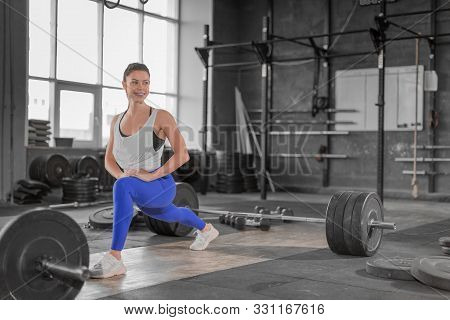 Smiling Woman Diong Stretching Exercises In Gym Before Workout. Healthy Lifestyle And Motivation Con