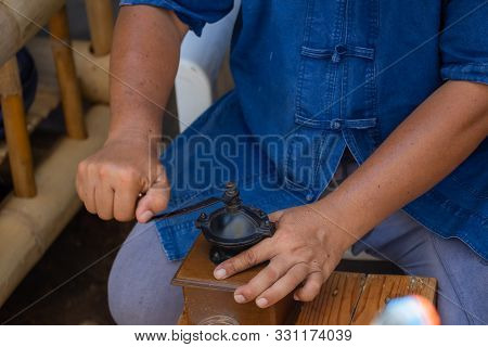 Man Grinds With An Old Coffee Mill With Crank Fresh Coffee Powder For Coffee.