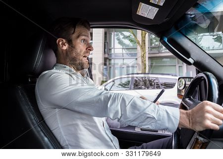 A Middle Aged Caucasian Man Distracted Driving While Using A Mobile Device Stops His Vehicle Suddenl