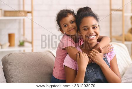 Sincere Love. Happy African American Sisters Hugging At Home, Empty Space