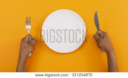 Hunger Concept. Black Woman Impatiently Waiting For Food With Empty Plate And Holding Fork And Knife