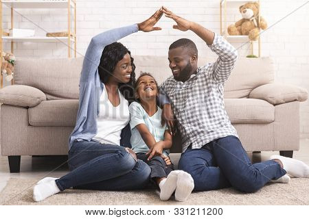 Adoption Concept. African American Foster Family Making Symbolic Roof Of Hands Gesture Above Little