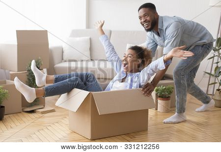 Excited African American Man Riding Woman In Cardboard Box Celebrating Moving Into New House. Select