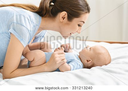 Speech And Language Development For Babies. Young Mother Playing With Her Cute Newborn Baby In Bed,