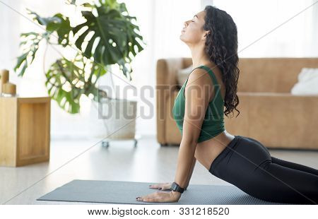 Athletic Young Girl Doing Yoga Or Stretching Exercises On Mat At Home, Light Interior, Copy Space
