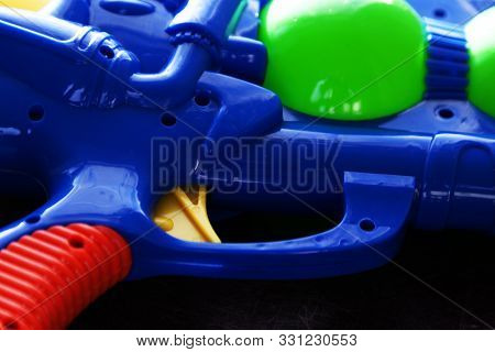 trigger for a blue plastic water gun lying on dark background poster