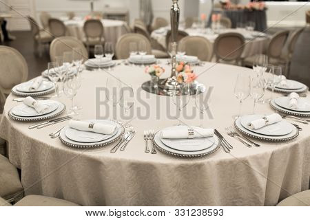 The White Round Banquet Table In The Restaurant Is Decorated With Fresh Flowers. Stylish Event Decor