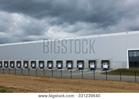 Production Building, Warehouse. Sky With Thunderclouds. Industrial Building