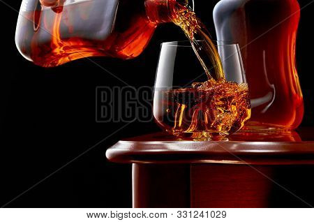 A Glass Of Whiskey With A Double Shot Of Whiskey And Ice On A Wooden Table. In The Background, A Ful