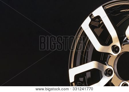 item spokes close-up aluminum die-cast alloy wheel for powerful SUV close-up on black background. polished surface. copyspace left. poster