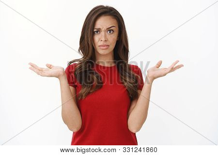 Questioned And Frustrated Disappointed Brunette Female In Red T-shirt Raise Eyebrow Skeptical And Su