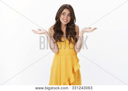 Awkward Reluctant Young Brunette In Yellow Dress, Look Away Embarrassed Shy, Shrugging And Spread Ha