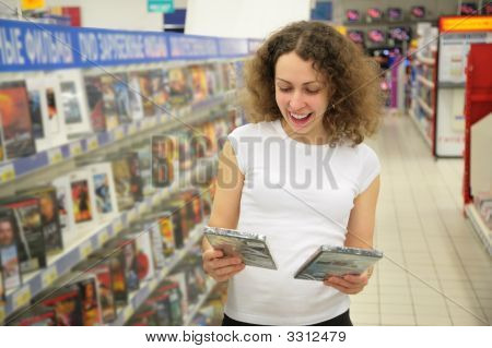 Young Woman In The Shop Chooses Disk
