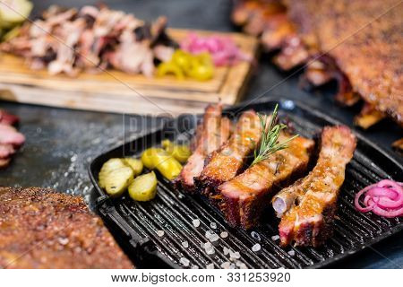 Grill Restaurant. Closeup Of Smoked Pork Ribs On Griddle Pan. Pulled Pork And Ribs In Background.