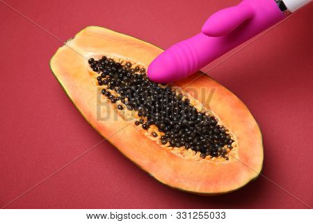 Half Of Papaya And Purple Vibrator On Red Background, Above View. Sex Concept