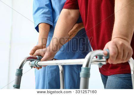 Caretaker Helping Elderly Man With Walking Frame On Light Background, Closeup