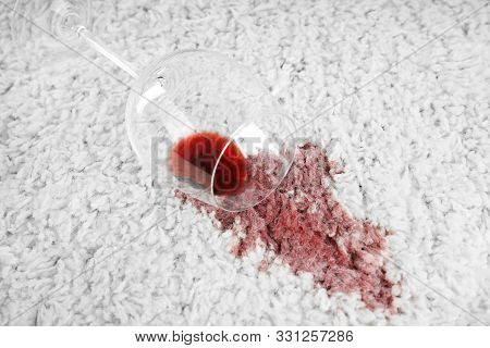 Overturned Glass And Spilled Exquisite Red Wine On Soft Carpet