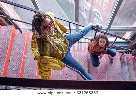 Two Young Beautiful Girls On The Stairs Top View. Modern Teenagers. Cocky Teen Millennial