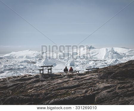 Two People Sitting With View Towards Icefjord In Ilulissat. Easy Hiking Route To The Famous Kangia G