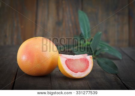 Fresh Grapefruits With Leaves Isolated On Wooden Background.two Ripe, Juicy Grapefruits, One Cut.