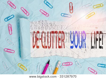 Word writing text De Clutter Your Life. Business concept for remove unnecessary items from untidy or overcrowded places Stationary and torn cardboard placed above a wooden classic table backdrop. poster