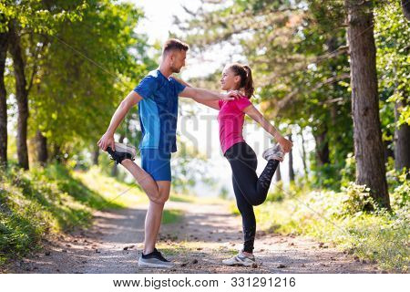young happy couple enjoying in a healthy lifestyle warming up and stretching before jogging on a country road through the beautiful sunny forest, exercise and fitness concept