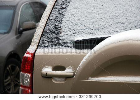 Back View Of Car Covered With First Snow. Slippery Roads, Dangerous Weather For Driving.